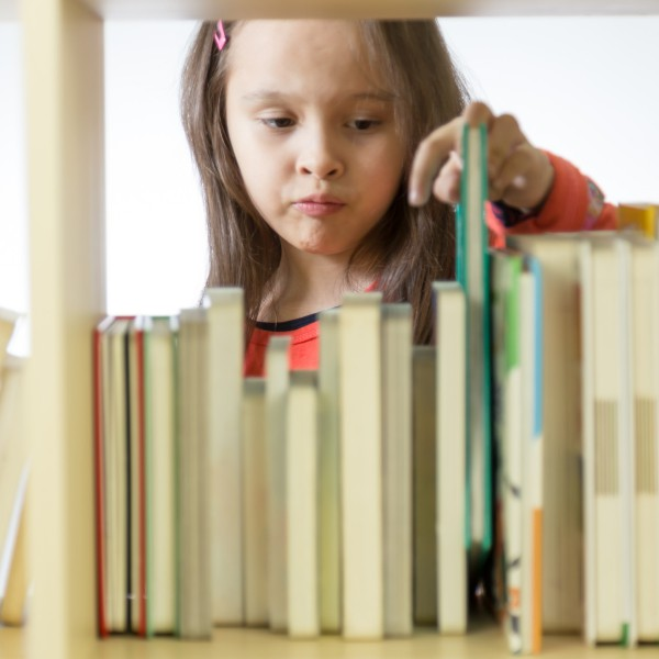 Young child perusing books on a bookshelf.