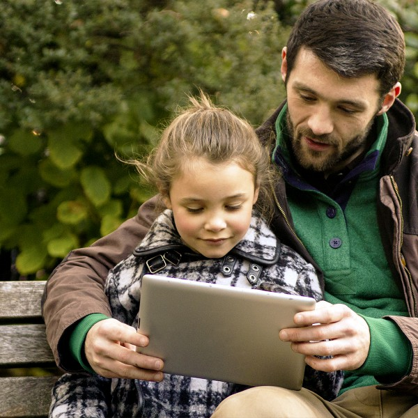 Father and daughter using a tablet while at the park.