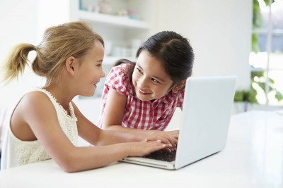 Two Young Girls Using Laptop At Home