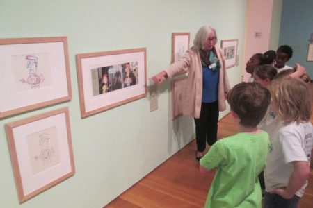 Students listen as a museum docent talks about the art of Mo Willems.