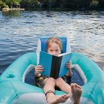 Young reader floating on a raft in a lake.