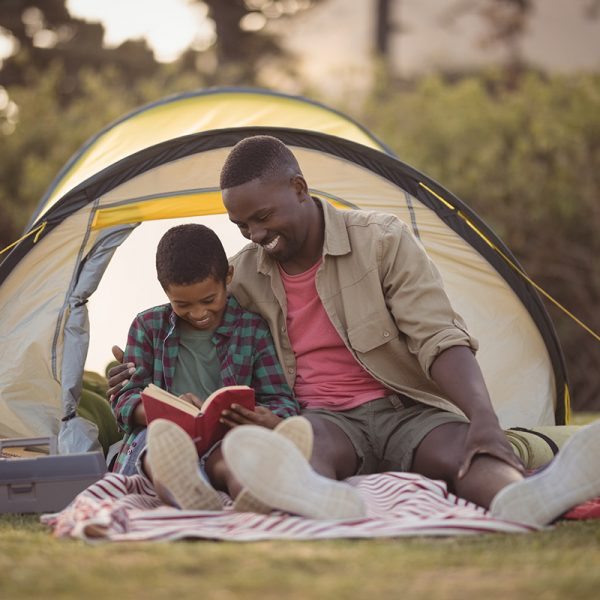 Father and son reading outside of a camping tent..