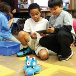 Two students programmng the Dash robot.