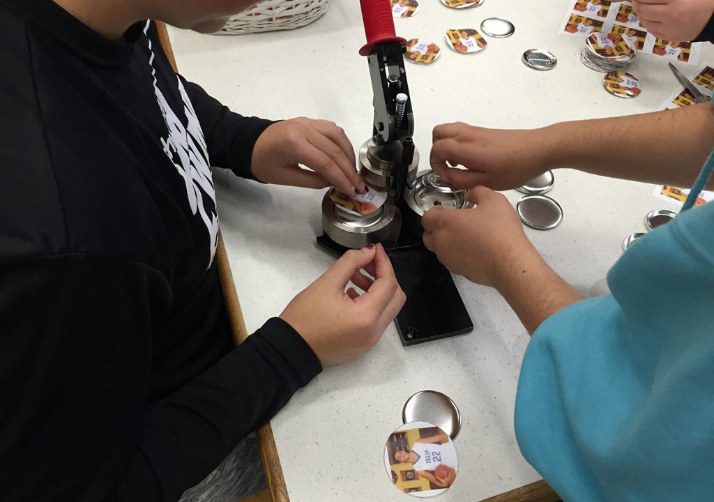 Students making memorial buttons in the school makerspace.