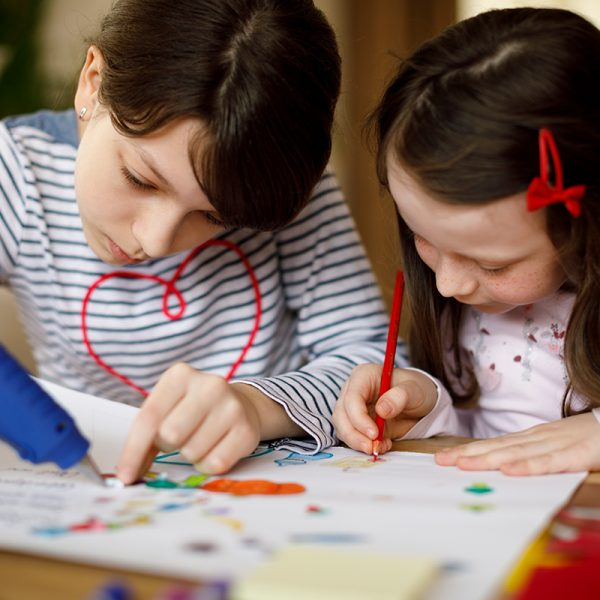 Two young students coloring and gluing crafts.