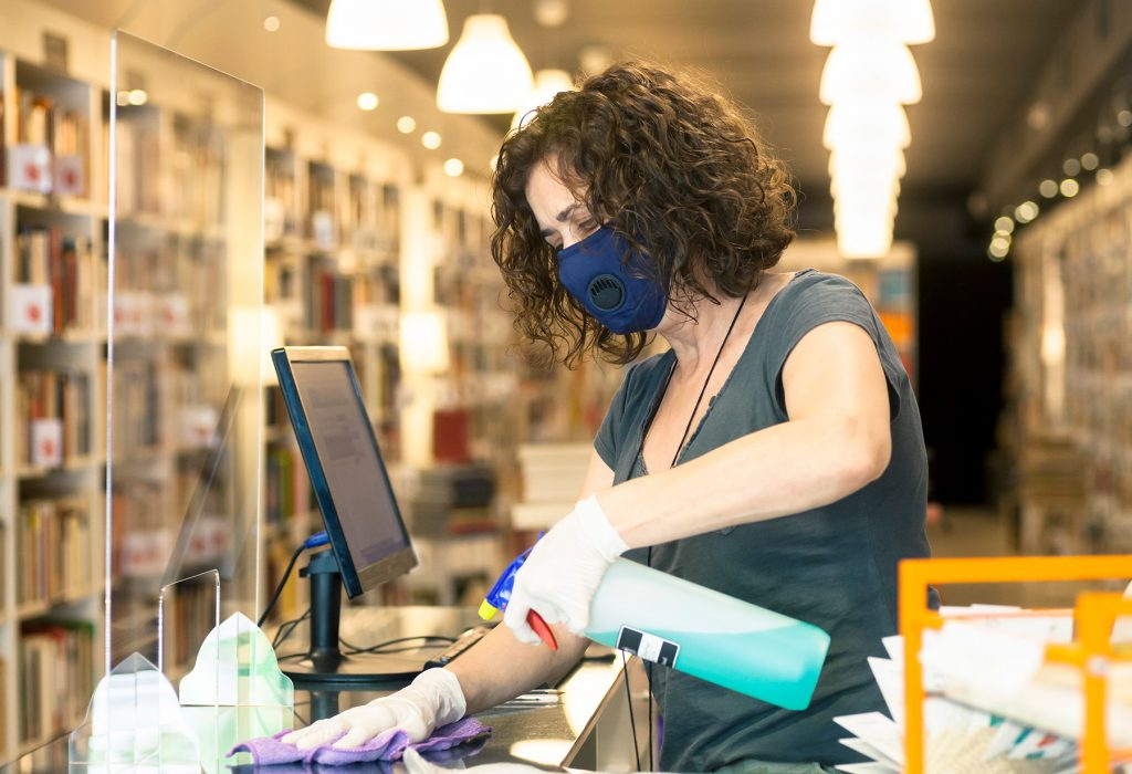 A librarian follows her planning guide to quarantine books and clean the service counter.