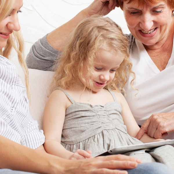 Mom, grandma, and child playing with an ipad.