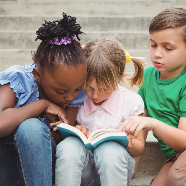 Friends reading a book together.