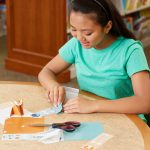 GIrl folding origami bookmarks.